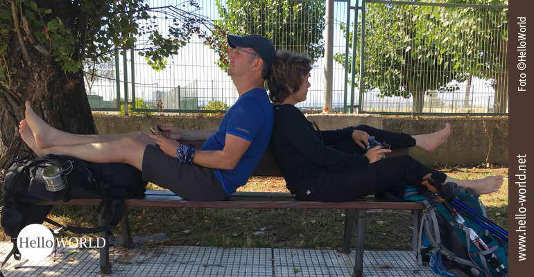 Das Bild von unserer siebten Camino Portugues Etappe zeigt ein Pärchen Rücken an Rücken auf der Parkbank sitzend und Pause machend.