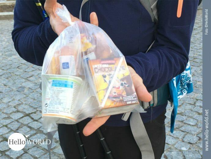 Dieses Bild vom Morgen unserer dritten Camino Portugues Etappe, die von Fao nach Viana do Castelo führt, zeigt ein kleines Frühstückspaket mit Jogurth und Schokolade im Plastikbeutel.