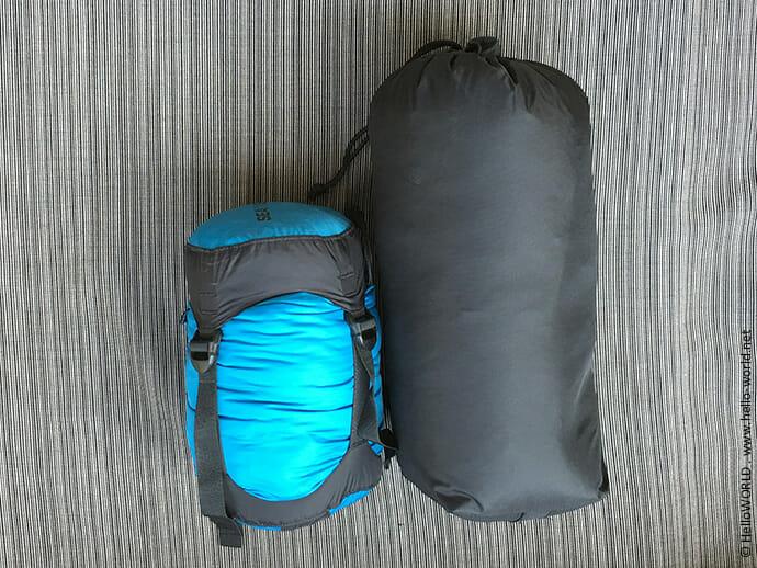 Das Bild zeigt einen Schlafsack in einem Aufbewahrungssack und daneben einen Schlafsack, der mit einem Spezialbeutel komprimiert wurde.