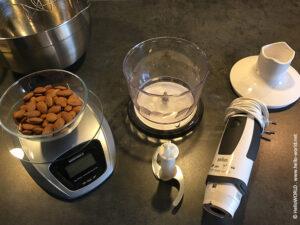 Das Bild zeigt Mandeln, eine Waage und einen Mixer