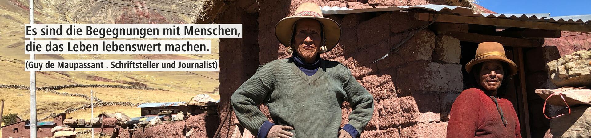 Dieses Bild zeigt einen Mann und eine Frau vor ihrem einfachen Haus in den Bergen Perus