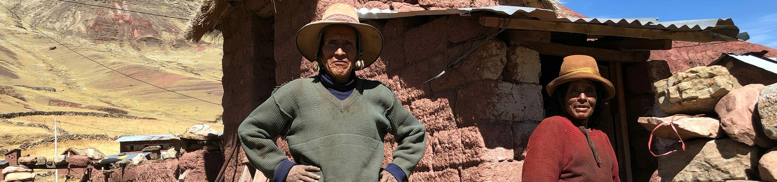 Dieses Startbild der HelloWorld-Kategorie Begegnungen stammt aus Peru und zeigt ein altes Paar, gekleidet mit Hüten vor ihrer steinernen Hütte stehend.