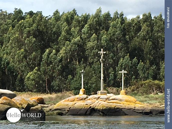 Auf der Caminho Portugues-Seeroute von der Ria de Arousa entlang des Flusses Rio Ulla stehen drei Kreuze auf gelblichen Felsen, im Hintergrund sind Bäume.