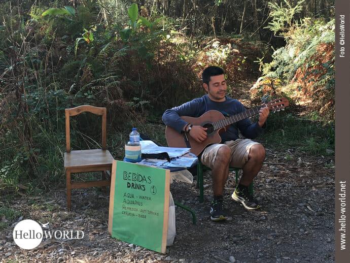 Auf der 9. Caminho Portugues-Etappe treffen wir Pablo. Er sitzt auf einem Stuhl und spielt Gitarre. Vor ihm ein Tisch mit Musik-CDs und Wasserflaschen, die er verkauft.