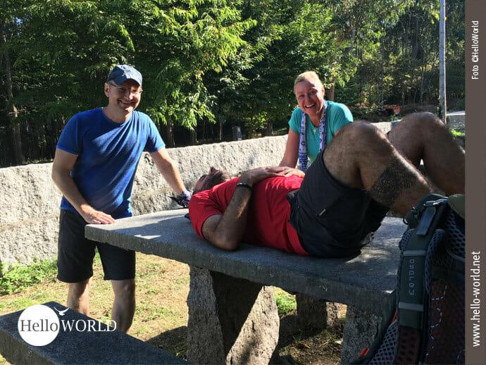 Nico und Margy stehen lachend neben Tom, der auf einem steinernen Tisch am Wegrand des Caminho Portugues liegt und mit Gummibällen unterm Rücken Verspannungen wegrollt.