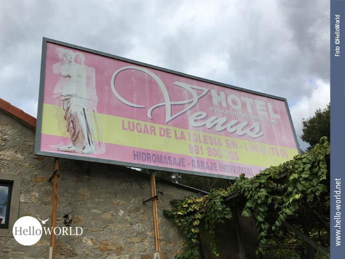 Das Bild zeigt den Caminho Portugues von seiner weltlichen Seite: Ein großes pink-gelbfarbenes Plakat, angebracht an einer Hauswand, macht auf das Motel Venus aufmerksam.