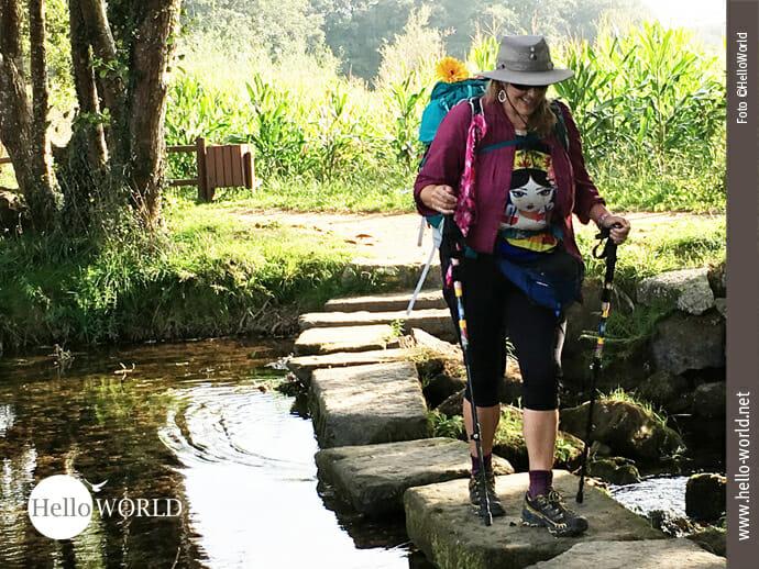 Auf dem Bild sieht man unsere Pilgerbekanntschaft Kerri aus Sacramento, bekleidet mit Hut und Rucksack geht sie über die Steine, die über den Fluss führen.