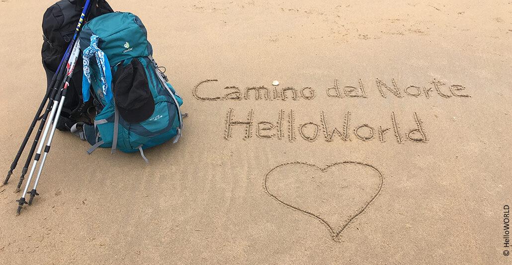 Hier sieht man Sand mit der Inschrift Camino del Norte HelloWorld und einem Herzsymbol.