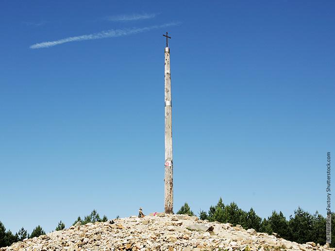 Auf dem Bild sieht man das Cruz de Ferro, ein kleines Eisenkreuz auf einem langen Baumstamm befestigt, dahinter strahlend blauer Himmel.