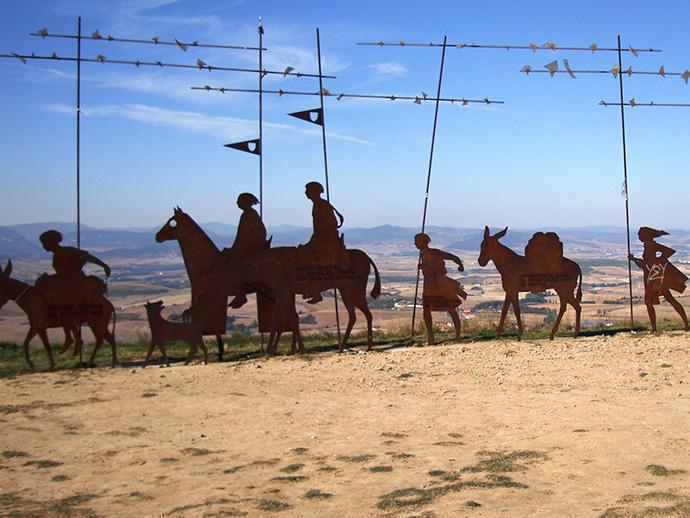 Das Bild zeigt Skulpturen in Form eines Pilgerzugs auf einem Berg in der Nähe von Pamplona