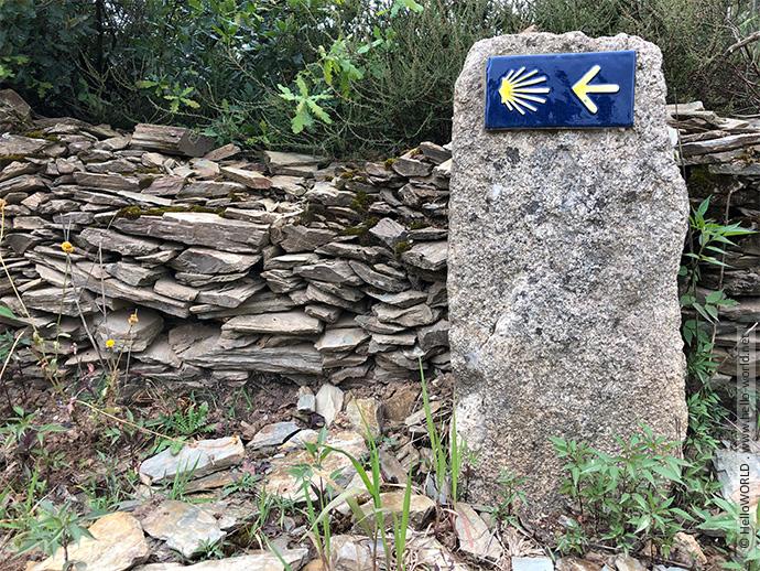 Hier sieht man ein Wegzeichen mit Muschel und Pfeil auf dem Camino Frances.