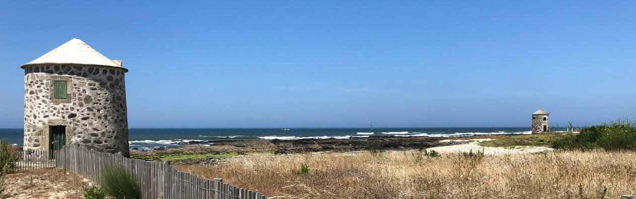 Das Bild zeigt einen Küstenabschnitt auf dem Jakobsweg Camino Portugues an dem zwei alte Steinmühlen stehen.