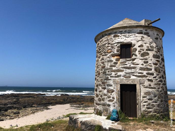 Auf diesem Foto sieht man eine alte Steinmühle, die in Portugal am Uferrand des Atlantiks steht.