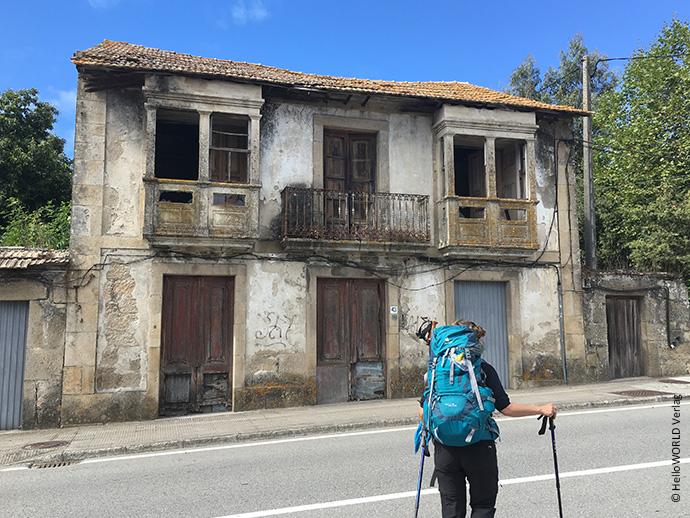 Hier sieht man eine Pilgerin auf dem Camino Portugues an einer Landstraße, ein zerfallenes Haus im Hintergrund.