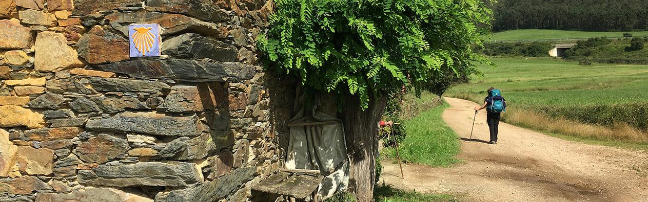 Das Bild stammt vom Jakobsweg Camino Portugues Rundwanderweg und zeigt eine Wanderin, die an einem Steinhaus vorbei geht.