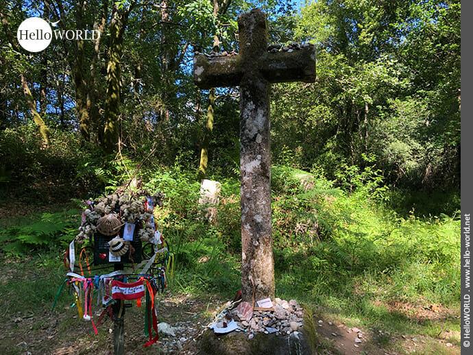 """Bunte """"Opfergaben"""" an einem Steinkreuz"""