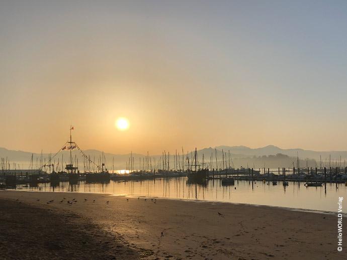 Hier sieht man ein Bild vom Sonnenuntergang am Hafen von Baiona, einem Etappenziel des Camino Portugues Küstenwegs.