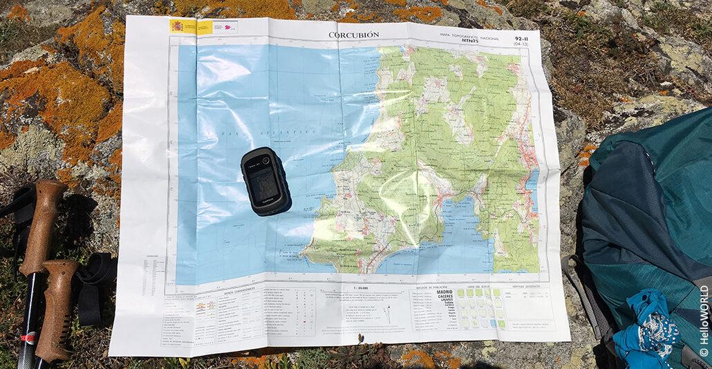 Hier sieht man eine ausgebreitete Landkarte, auf der ein GPS-Gerät liegt.