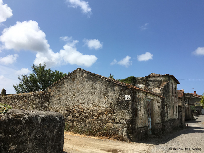Auf diesem Bild sieht man eine Dorfstraße in Portugal mit alten Häusern bei blauem Himmel.