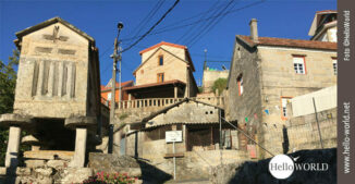 Hier sieht man einen Weg auf dem Camino Portugues, der bei strahlend blauem Himmel aufwärts zu den steinernden Häusern von Ponte Sampaio führt.