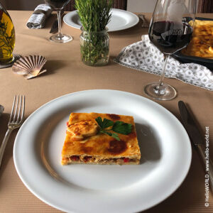 Hier sieht man ein Stück Empanada gallega mit Thunfisch auf einem gedeckten Tisch.