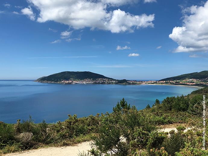 Das Bild zeigt den Blick auf Finisterre an der Ria Corcubion bei blauem Himmel.