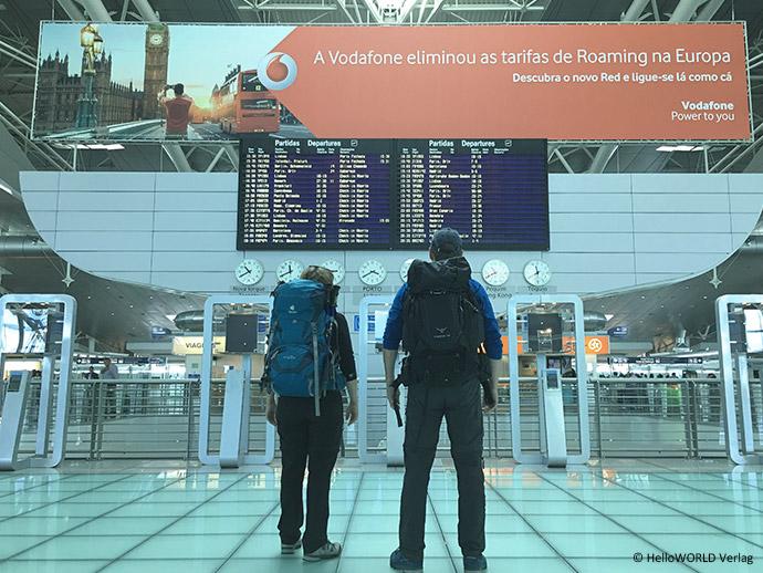 Hier sieht man zwei Personen mit Rucksack die auf dem Flughafen Porto vor der Anzeigetafel stehen.