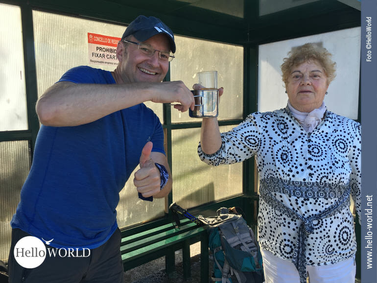 An einer Bushaltestelle entlang des Caminho Portugues lädt uns die Spanierin Josefa auf eine Flasche Wein ein und Nico stößt freudig mit ihr an.