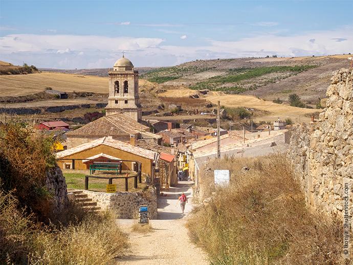 Hier sieht man den Blick auf das Dorf Hontanas, in dem gerade eine Pilgerin mit Rucksack auf eine sandigen Straße entlang läuft.