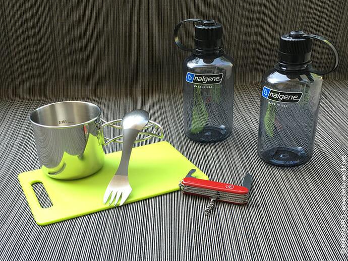 Das Bild zeigt verschiedene Utensilien wie Trinkflaschen oder Taschenmesser für die Verpflegung auf dem Jakobsweg.