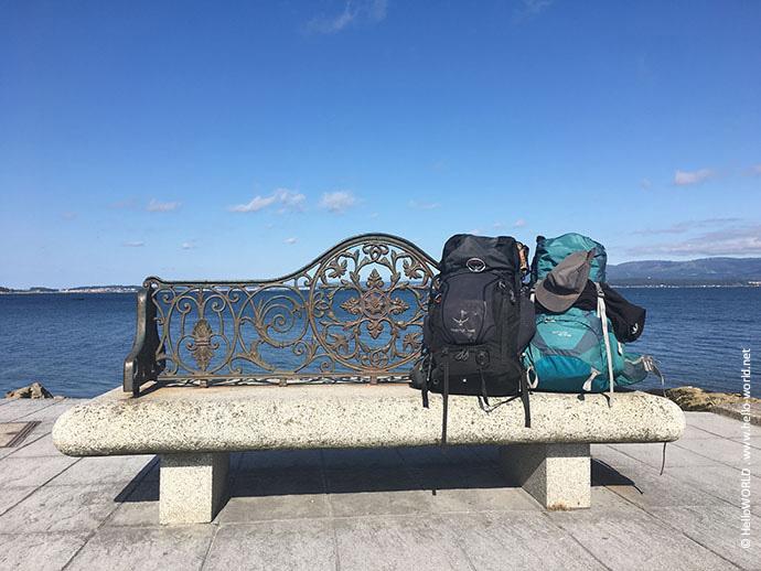 Hier sieht man zwei Rucksäcke, die auf einer Bank auf dem Jakobsweg Camino Portugues stehen.