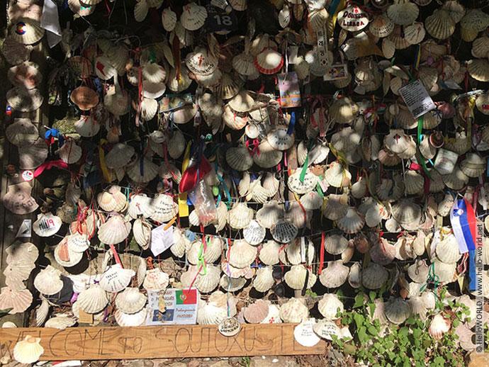 Hier sieht man eine Wand voller Jakobsmuscheln, das Erkennungszeichen auf dem Jakobsweg.