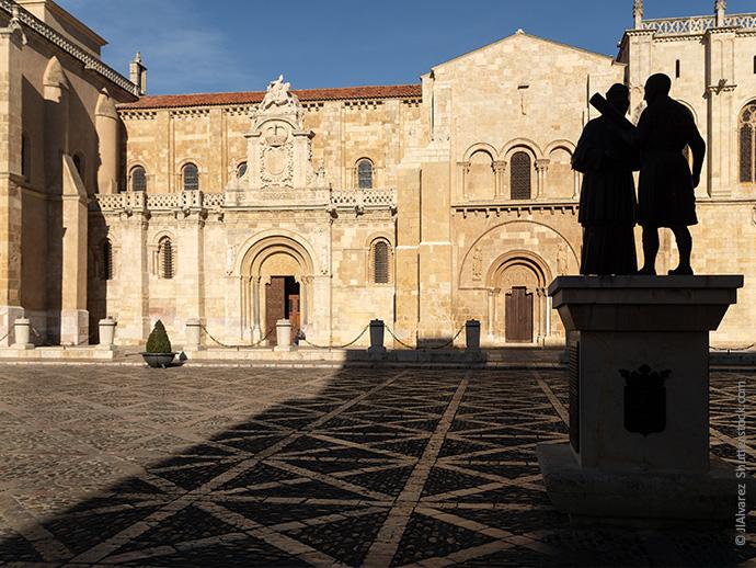 Dieses Bild zeigt die Basilica San Isodoro in Leon im Sonnenlicht, davor eine Skulptur mit zwei Menschen im Schatten.