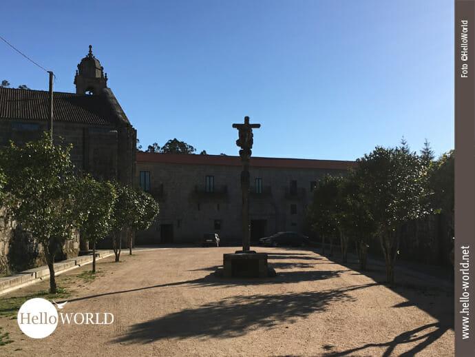Ziel der 9. Caminho Portugues-Etappe: Hier sieht man im Sonnenschein den großen Vorplatz des Mosteiro de Armenteira, in der Mitte ein großes Kreuz, gesäumt von Bäumen.