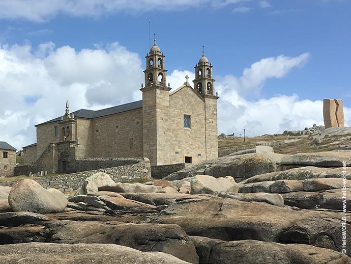 Das Bild zeigt das Heiligtum Virxe da Barca, eine Kirche in Muxia, Galicien, die direkt an der Küste steht.
