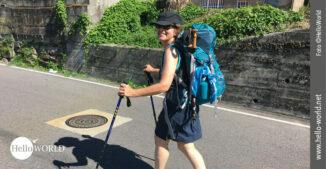 Bei der achten Camino Portugues Etappe pilgert Andrea freudestrahlend im Sonnenschein mit ihrem Rucksack bepackt durch die Straßen kleiner Dörfer.