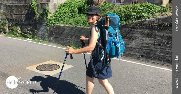 Bei der achten Caminho Portugues Etappe pilgert Andrea freudestrahlend im Sonnenschein mit ihrem Rucksack bepackt durch die Straßen kleiner Dörfer.