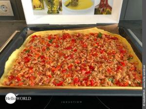 Hier sieht man den Boden und die Füllung der Empanada auf einem Backblech vorbereitet.
