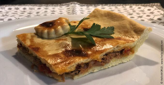 Auf diesem Foto sieht man ein Stück Empanada mit Thunfisch auf einem Teller angerichtet.