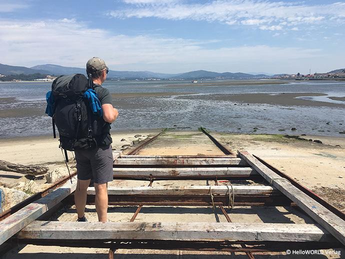 Hier sieht man einen Mann mit Rucksack, der sehnsüchtig auf das Wasser blickt.