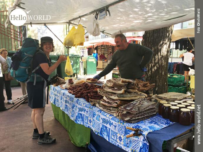 Das Bild entstand am Ende der dritten Camino del Norte Etappe in Ribadeo auf dem Wochenmarkt und zeigt eine Rucksackreisende mit Kostproben in der Hand.