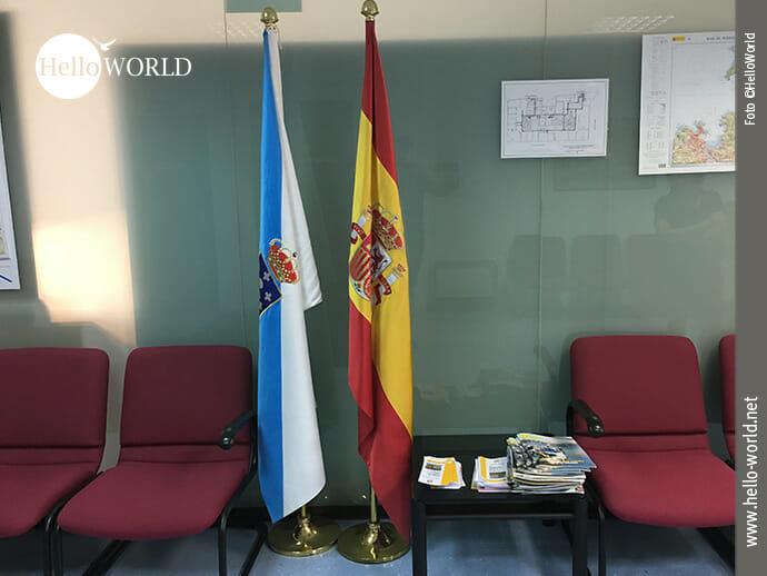 Das Bild zeigt den Warteraum des Instituto Geografico Nacional mit den Nationalflaggen von Spanien und Galicien und roten Sesseln.