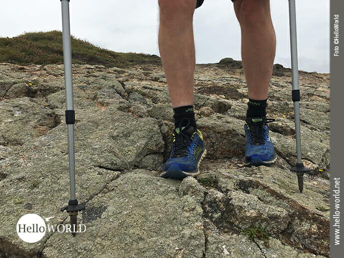 Das Bild von der fünften Camino del Norte Etappe zeigt zwei Beine auf einem Felsen stehend mit Turnschuhen und Stöcken.