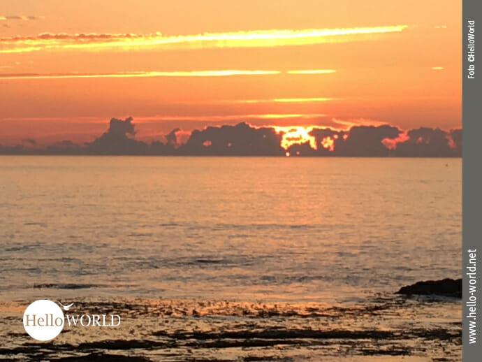 Diese Aufnahme von der fünften Camino del Norte Etappe zeigt einen Sonnenuntergang auf dem Atlantik mit tiefrot und gelbenen Strahlen.