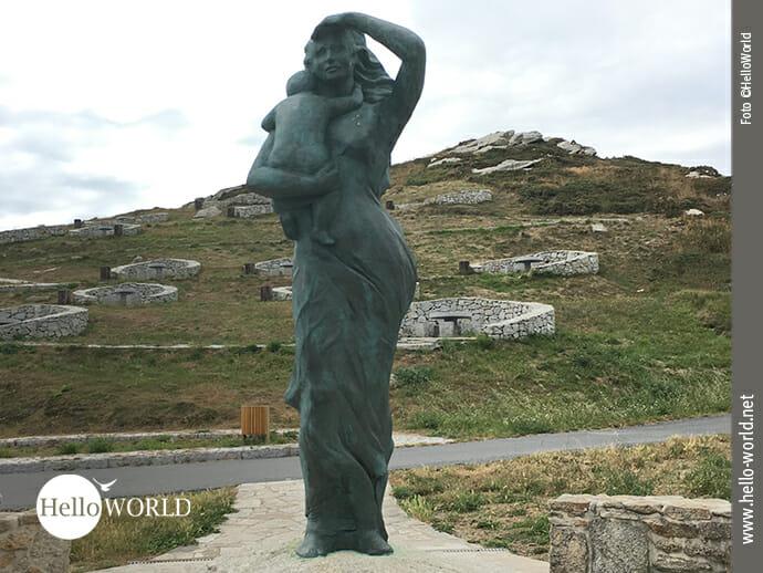"""Das Bild von der Costa da Morte zeigt das Denkmal """"A Espera"""" – zu Deutsch warten/hoffen - bei Laxe, wo eine Frau mit ihrem Kind in der Hand sehnsüchtig auf das Meer blickt und auf das Schiff wartet."""