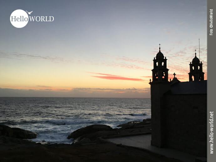 Das Bild von der sechsten Camino del Norte Etappe zeigt die Umrisse der Wallfahrtskirche Santuario da Virxe da Barca in Muxia vor einem Sonnenuntergang.