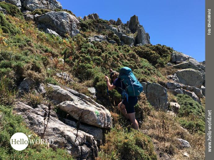 Das Bild zeigt eine Wanderin an der spanischen Nordküste wie sie den Berg zwischen Felsen hinauf geht.