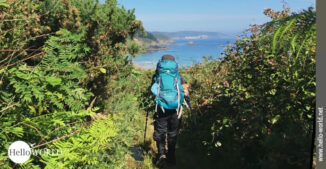 Das Bild zeigt eine Frau mit türkisfarbenen Rucksack auf einem stark bewachsenen Weg an der spanischen Nordküste.