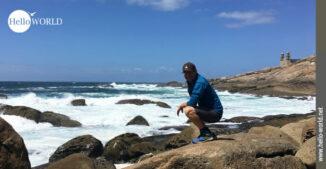 Das Bild von der Costa da Morte an der Steilküste Muxia zeigt einen Mann in der Hocke auf einem Felsen direkt vor dem Wasser sitzend.