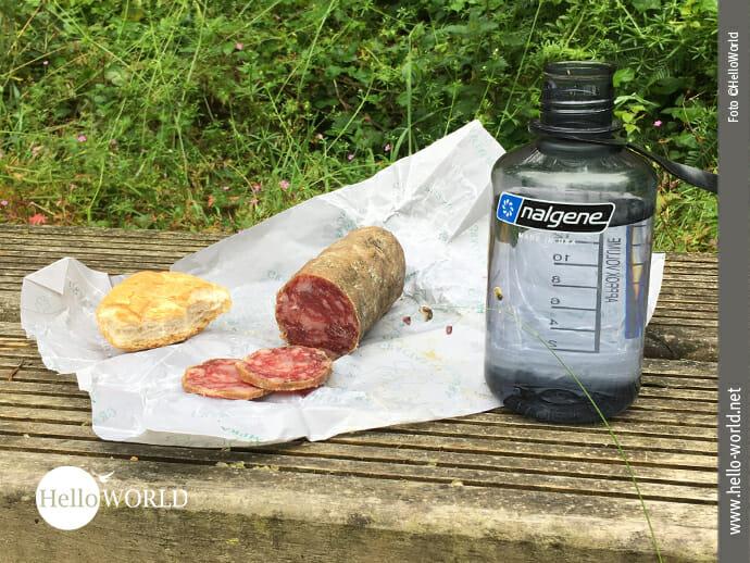 Das Bild zeigt die Verpflegung während einer Wanderung an der spanischen Nordküste: Salami, Brötchen, eine Wasserflasche stehen auf einer Holzbank.